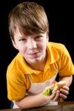吃三明治的滑稽的男孩 库存图片