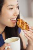 吃与一杯咖啡的年轻亚裔妇女酥皮点心 库存照片