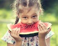 吃与乐趣幽默神色的美丽的孩子女孩大红色西瓜 免版税库存图片
