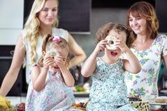 吃与他们的孩子的俏丽的妇女甜点 库存照片