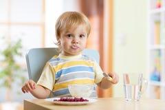 吃与匙子的儿童小男孩食物在托儿所 库存照片