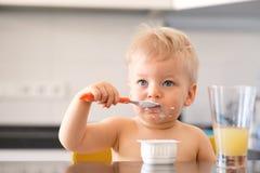 吃与匙子的可爱的一个岁男婴酸奶 库存照片