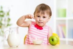 吃与匙子的孩子食物  免版税库存图片