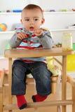 吃与匙子的孩子婴儿食品 库存图片