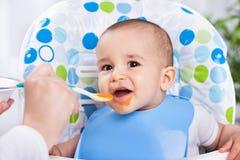 吃与匙子的微笑的愉快的婴孩 免版税库存照片