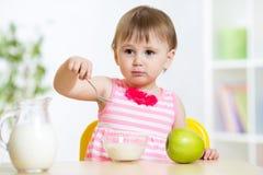 吃与匙子的愉快的儿童女孩食物  库存图片