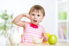 吃与匙子的愉快的孩子女孩食物  库存图片