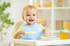 吃与匙子的愉快的婴孩孩子男孩食物  免版税库存图片