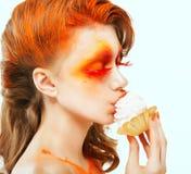 上色。 创造性。 吃与奶油的红发妇女档案一个蛋糕。 脸红 免版税库存图片