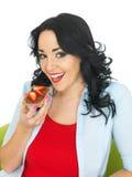 吃与巧克力传播和新鲜的切的草莓的少妇整粒薄脆饼干 图库摄影