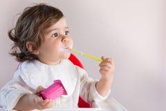 吃与杂乱面孔的女婴酸奶 库存图片