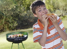 吃与烤肉格栅的男孩烟熏腊肠在背景中 免版税库存图片