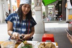 吃与菜和甜调味汁的旅客泰国妇女中国街道食物油豆腐在老镇餐馆在潮州 库存图片
