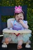 吃与紫色结霜的第一生日蛋糕和在她的头的女婴桃红色冠 免版税库存图片