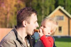 吃两的父亲和儿子一个百吉卷 库存照片