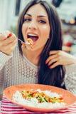 吃中国食物的少妇在餐馆,有她的lunc 免版税库存图片