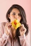 吃中国馄饨薄脆饼干的年轻深色的女孩 免版税图库摄影