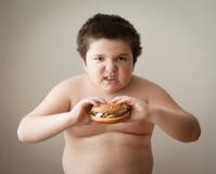 吃乳酪汉堡的儿童男孩孩子肥胖汉堡饮食 免版税库存照片