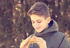 吃乳酪汉堡的年轻人 免版税库存照片