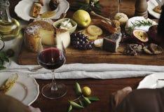 吃乳酪的盛肉盘人们用季节性果子和酒 免版税库存图片