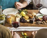 吃乳酪的盛肉盘人们用季节性果子和酒 免版税库存照片