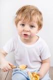吃乳酪蛋糕松饼的小男孩。 免版税库存图片