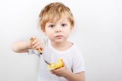 吃乳酪蛋糕松饼的小男孩。 库存图片
