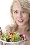 吃五颜六色的庭院沙拉的愉快的少妇 免版税库存图片