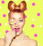 吃五颜六色的棒棒糖的秀丽女孩 图库摄影