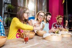 吃亚洲饭食的朋友在餐馆 免版税图库摄影