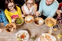 吃亚洲饭食的朋友 图库摄影
