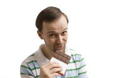 吃人年轻人的巧克力 免版税库存图片