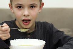 吃从一块板材的儿童男孩汤有匙子的 免版税图库摄影