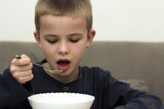 吃从一块板材的儿童男孩汤有匙子的 库存照片