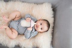 吃从瓶,在诞生以后的9个月的亚裔小婴儿牛奶 免版税库存照片