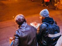 吃传统包裹的朋友在圣诞节圣诞节Marke 免版税库存图片