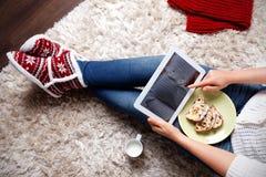 吃传统圣诞节曲奇饼的妇女 免版税库存照片