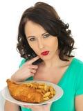 吃传统炸鱼加炸土豆片的少妇 库存照片
