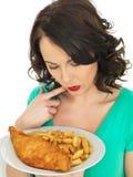 吃传统炸鱼加炸土豆片的少妇 免版税库存照片