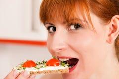 吃健康妇女的薄脆饼干 免版税库存图片