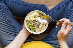 吃健康早餐碗 酸奶,荞麦,种子,在白色碗的新鲜水果在妇女` s手上 干净吃,节食,戒毒所 免版税库存照片