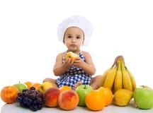 吃健康果子的甜美丽的小厨师 库存图片