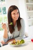 吃健康膳食的妇女在厨房里 库存图片