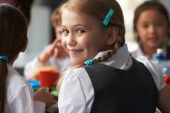 吃健康被包装的午餐的女孩在学校食堂 库存照片
