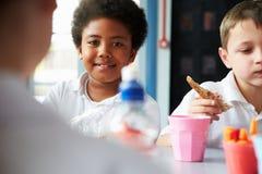 吃健康被包装的午餐的男孩在学校食堂 免版税库存图片