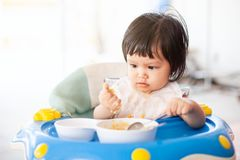 吃健康食品的可爱宝贝亚裔儿童女孩由她自己 免版税库存照片