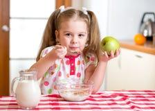 吃健康食物的孩子在厨房里 免版税库存图片