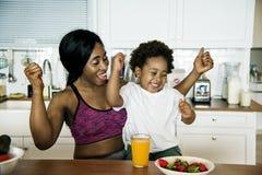吃健康食物的母亲和儿子在厨房里 库存图片