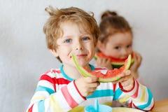 吃健康食物西瓜的小孩男孩和女孩 库存图片