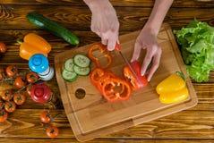 吃健康 妇女在家准备新鲜的沙拉的厨房里 免版税图库摄影